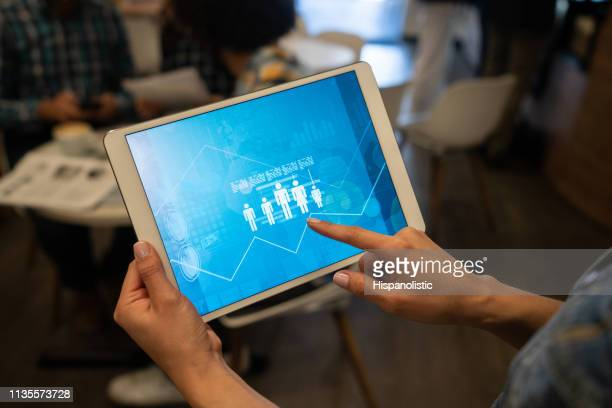 unrecognizable woman holding a tablet with inphographics displaying on screen - using digital tablet stock photos and pictures