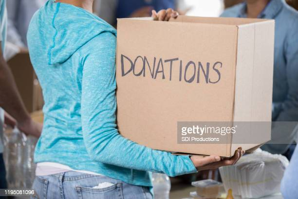 unrecognizable woman holding donation box - charitable donation stock pictures, royalty-free photos & images