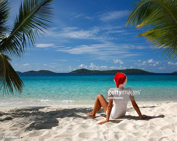 unrecognizable woman in santa hat on a beach - caribbean christmas stock pictures, royalty-free photos & images