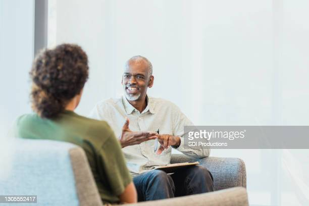 unrecognizable woman listens as cheerful counselor gestures and speaks - business casual stock pictures, royalty-free photos & images
