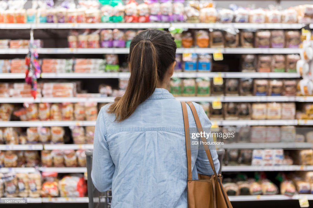 Unrecognizable woman marvels at grocery bread selection : Stock Photo