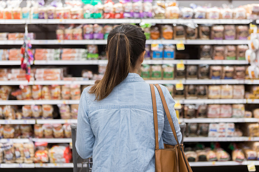 Unrecognizable woman marvels at grocery bread selection 1041147560