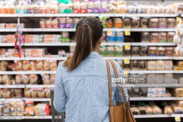 unrecognizable woman marvels at grocery bread selection - food and drink stock pictures, royalty-free photos & images