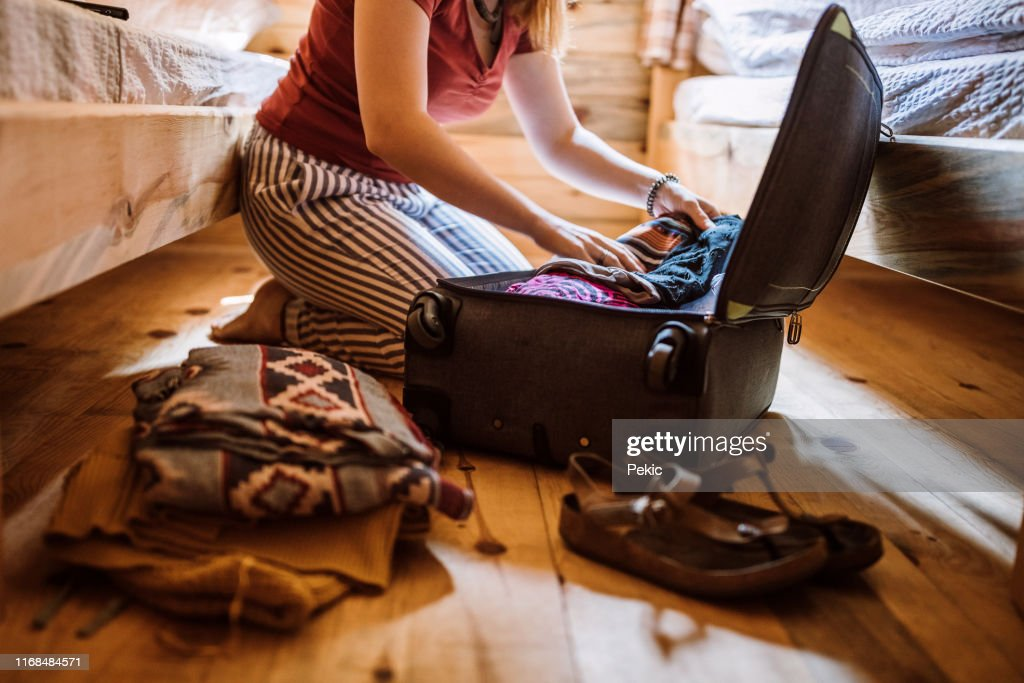 Unrecognizable woman packing luggage in log cabin : Stock Photo