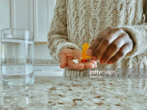 unrecognizable woman pours pills into hand from prescription bottle - painkiller stock pictures, royalty-free photos & images