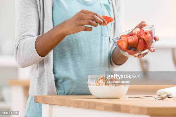 Unrecognizable woman prepares parfait at kitchen counter
