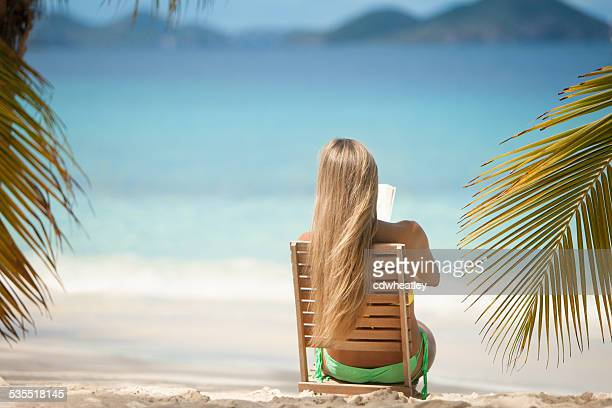 unrecognizable woman reading a book at the Caribbean beach