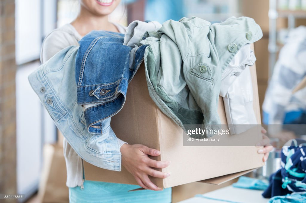Unrecognizable woman receives box of clothing during clothing drive : Stock Photo