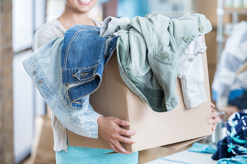 Unrecognizable woman receives box of clothing during clothing drive 832447866