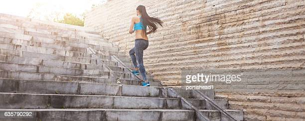 Unrecognizable woman running up on stairs