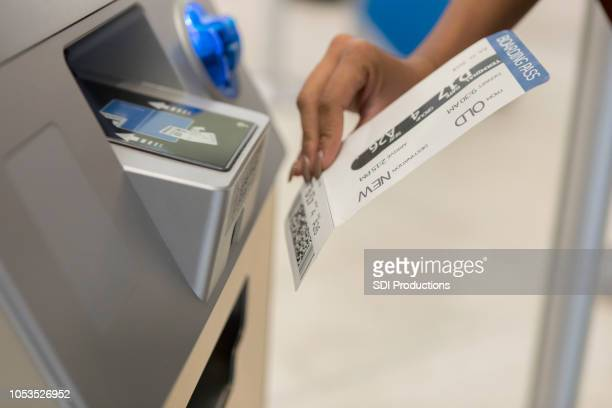 Unrecognizable woman scans boarding pass at airport kiosk