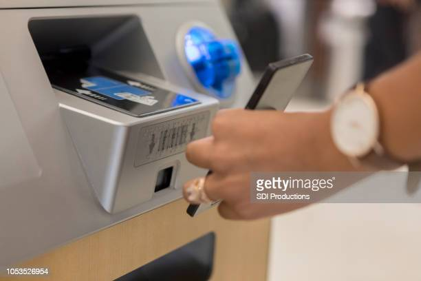 unrecognizable woman scans smart phone at airport kiosk - kiosk stock pictures, royalty-free photos & images