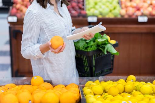 Unrecognizable woman shops for oranges - gettyimageskorea