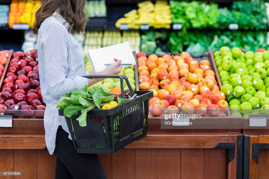 Unrecognizable woman shops for produce in supermarket : Stock Photo