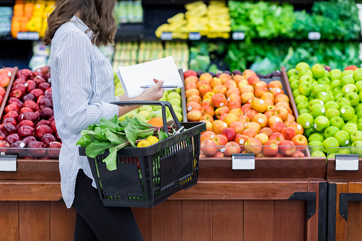 Unrecognizable woman shops for produce in supermarket 871227828