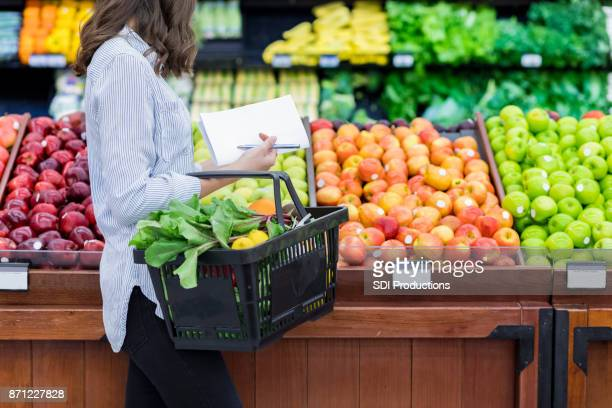 unrecognizable woman shops for produce in supermarket - apple fruit stock photos and pictures