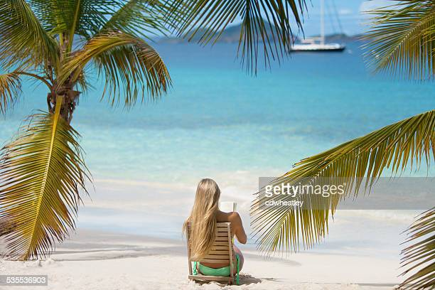 unrecognizable woman sitting in beach chair and reading a book