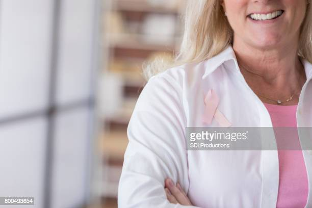 unrecognizable woman smiles while wearing breast cancer ribbon - women's issues stock photos and pictures