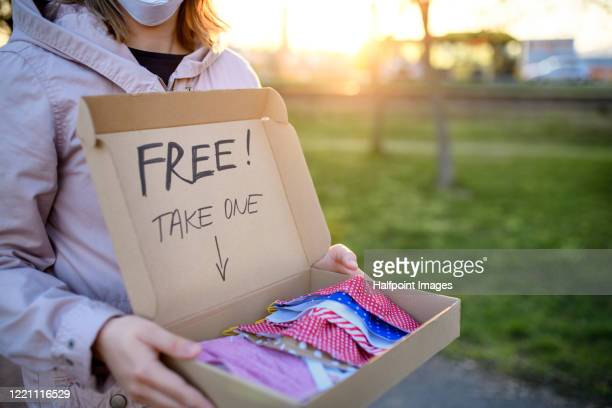 unrecognizable woman standing outdoors offering free protective face masks, corona virus concept. - free stock pictures, royalty-free photos & images