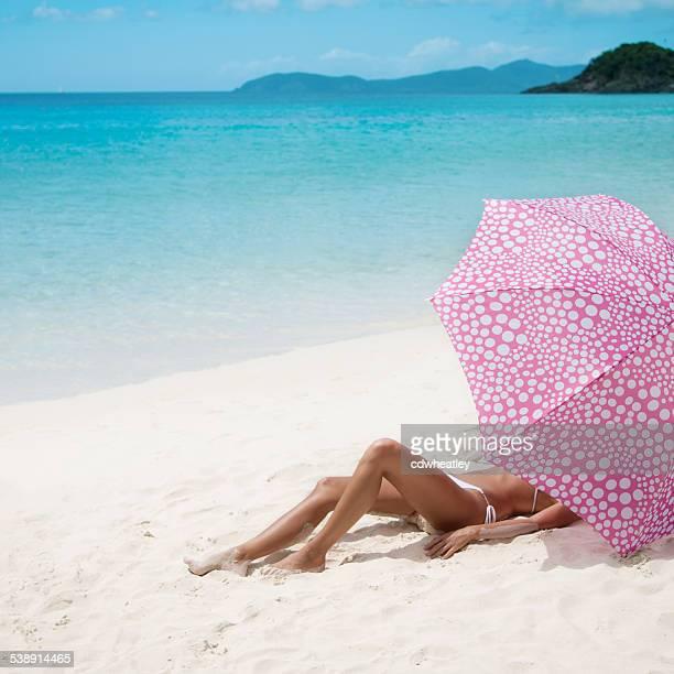 unrecognizable woman sunbathing under umbrella at a Caribbean beach