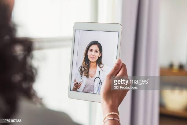 unrecognizable woman talks with doctor during telemedicine visit - doctor stock pictures, royalty-free photos & images