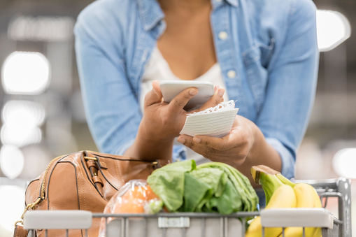 Unrecognizable woman texts while shopping for groceries - gettyimageskorea
