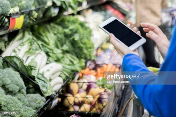 Unrecognizable woman uses mobile app in grocery store