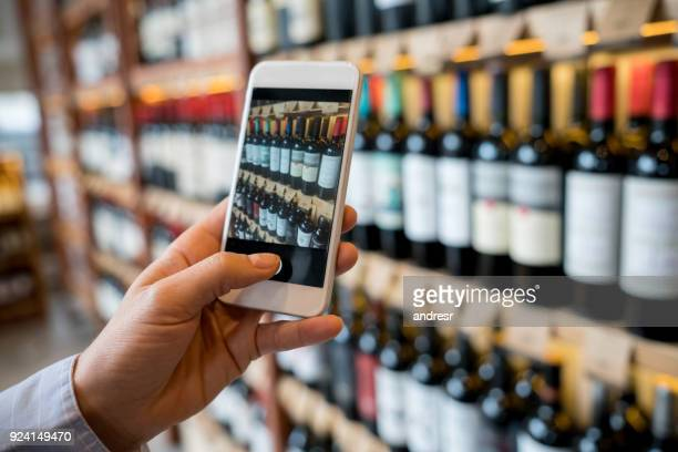 unrecognizable woman using a wine application on smartphone to read information about the wines - liquor store stock pictures, royalty-free photos & images