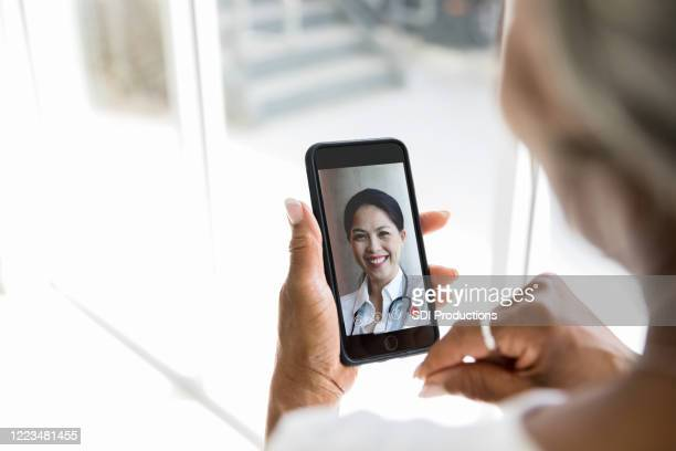 unrecognizable woman video chats with doctor - looking over shoulder stock pictures, royalty-free photos & images