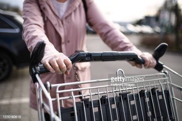 unrecognizable woman with gloves outdoors pushing shopping cart in parking lot. - parking stock pictures, royalty-free photos & images
