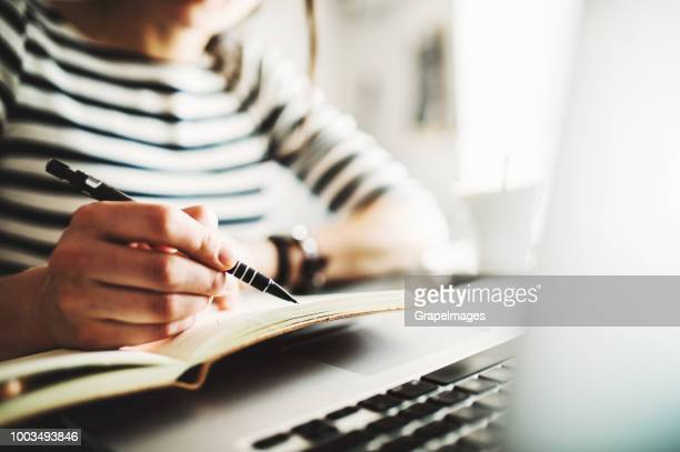 unrecognizable woman with laptop, a note pad and a pen sitting in a cafe, writing. close up. - scrivere foto e immagini stock