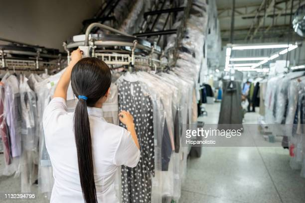 unrecognizable woman working at a laundry service looking for a clothing on conveyor belt - dry cleaner stock pictures, royalty-free photos & images