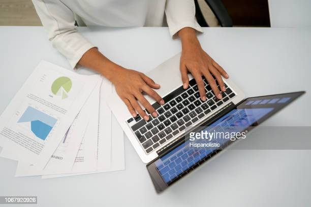 Unrecognizable woman working on laptop at the office