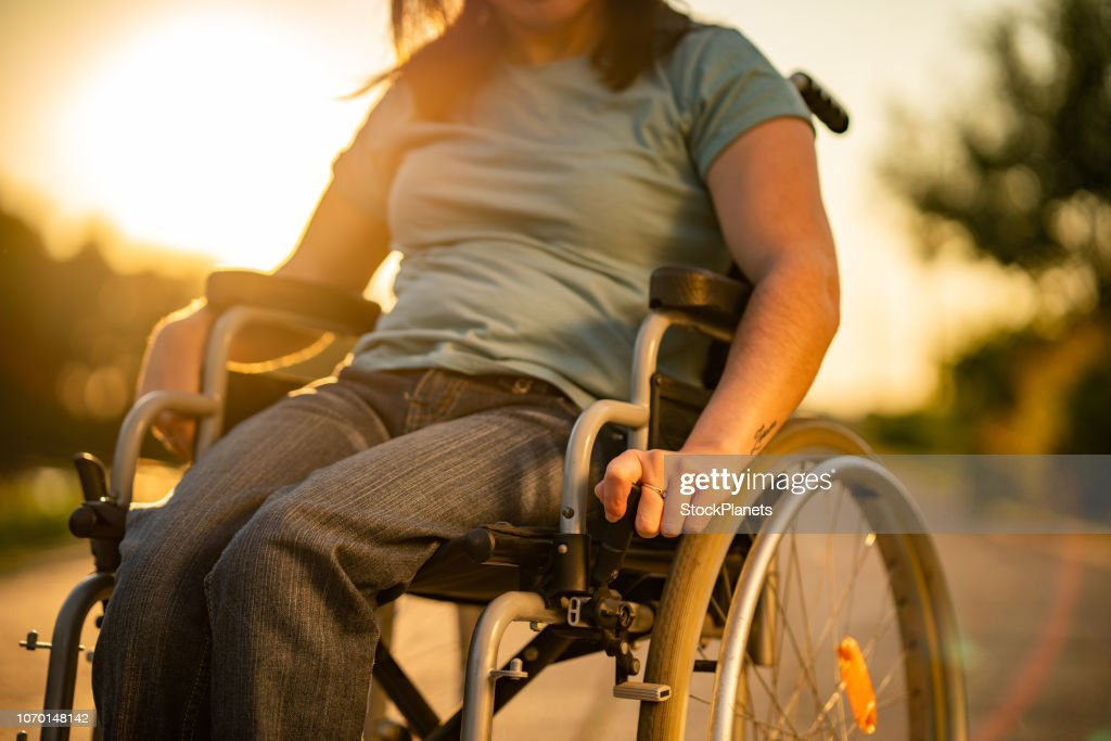 Unrecognizable women on a wheelchair at sunset : Stock Photo
