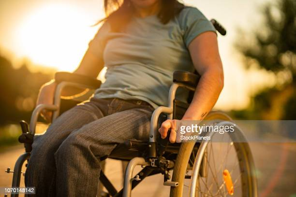 unrecognizable women on a wheelchair at sunset - paraplegic stock photos and pictures