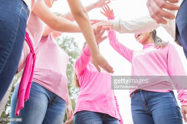 Unrecognizable women with hands together in unity