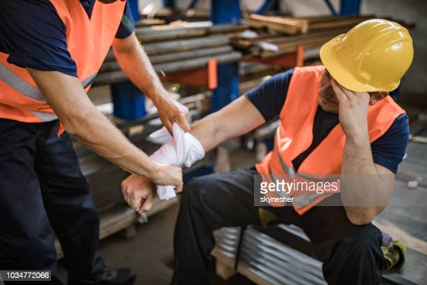 unrecognizable worker assisting his colleague with physical injury in steel mill. - acidentes de trabalho imagens e fotografias de stock