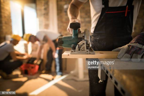 Unrecognizable worker cutting plank with circular saw at construction site.