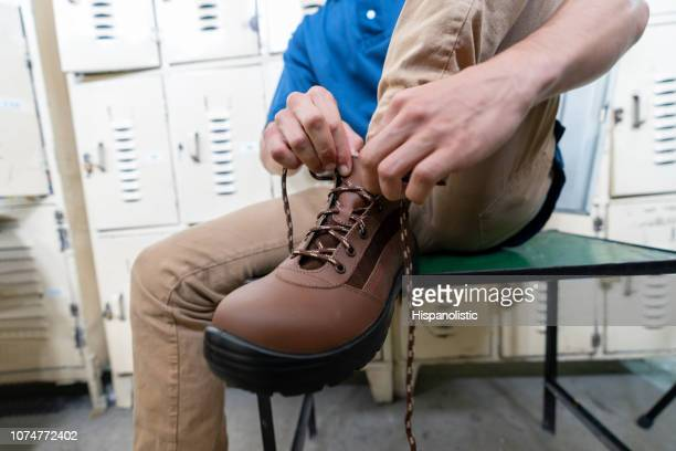 unrecognizable worker tying shoelace of work boot at locker room in a factory - shoe factory stock pictures, royalty-free photos & images