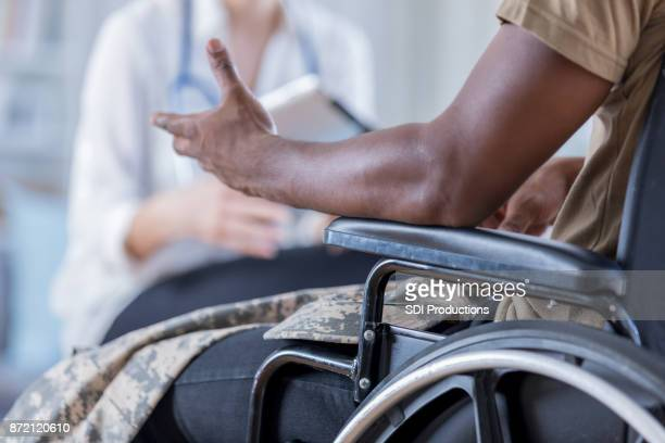 unrecognizable wounded warrior discusses symptoms with doctor - military doctor stock photos and pictures