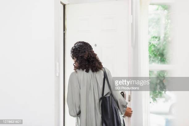 unrecognizable young adult woman leaves house carrying purse - leaving stock pictures, royalty-free photos & images