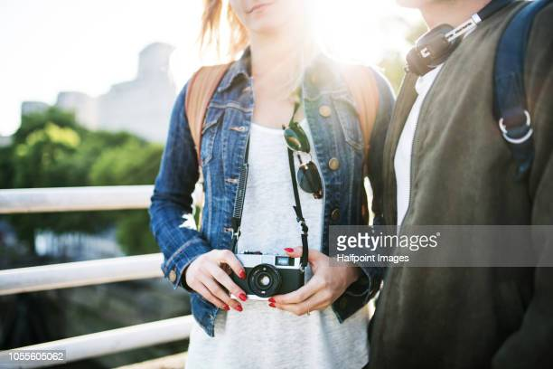 Unrecognizable young couple with camera walking on a bridge in a city at sunset.