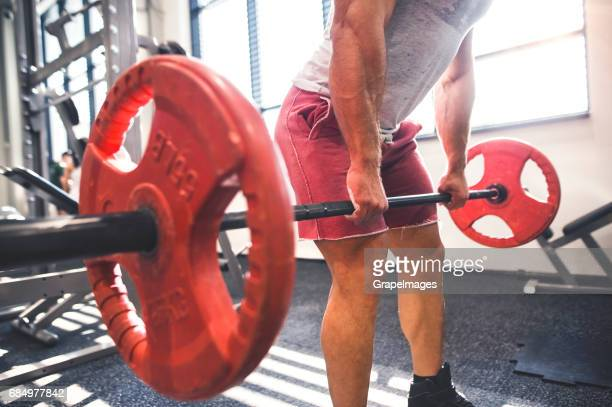 unrecognizable young fit man in gym working out with heavy barbell, doing dead lift - male bum stock pictures, royalty-free photos & images