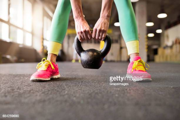 unrecognizable young fit woman in gym working out, holding kettlebell - pink shoe stock pictures, royalty-free photos & images