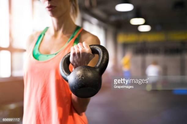 Onherkenbaar jonge past vrouw in de sportschool uit te werken, houden kettlebell