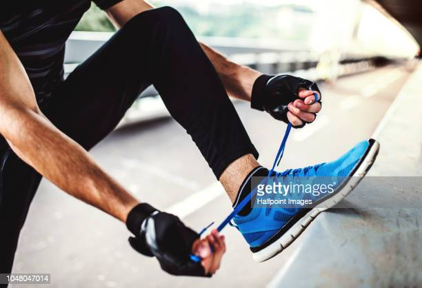 unrecognizable young sporty man with fingerless gloves tying shoelaces outdoors in the city. - blue shoe stock pictures, royalty-free photos & images