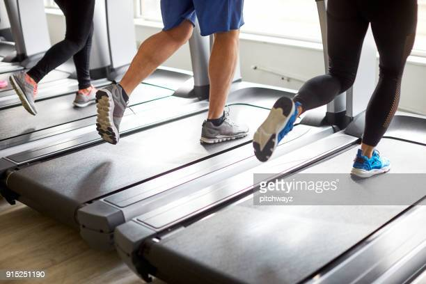 unrecognized people running on treadmill. - warming up stock pictures, royalty-free photos & images