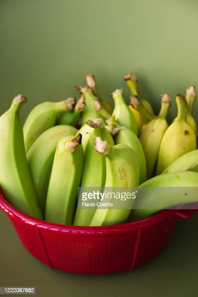 unripe bananas in red plastic bowl - unripe stock pictures, royalty-free photos & images