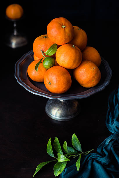 unripe mandarin with leaves. Chiaroscuro with green cloth