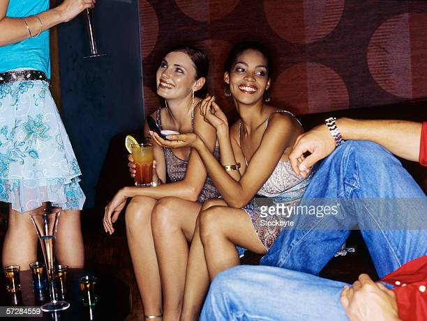 Unseen man looking at three young women drinking cocktails in bar